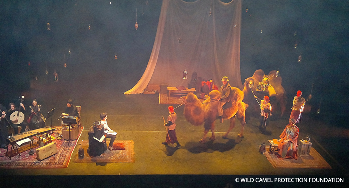 John rides on Therese the camel at the Opera house as Temujin follows in behind.