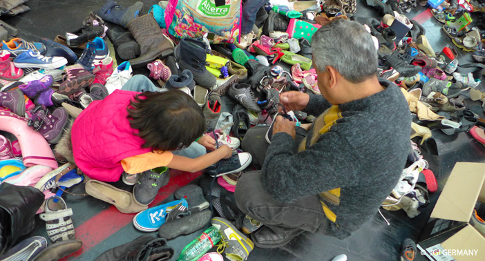 A young refugee girl tries to find her size shoes out of a pile of donated clothes.